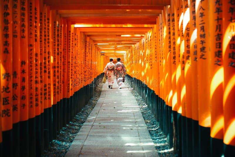 Donna giapponese in vestito dal kimono fra Tori Gate di legno rossa a Fus immagini stock