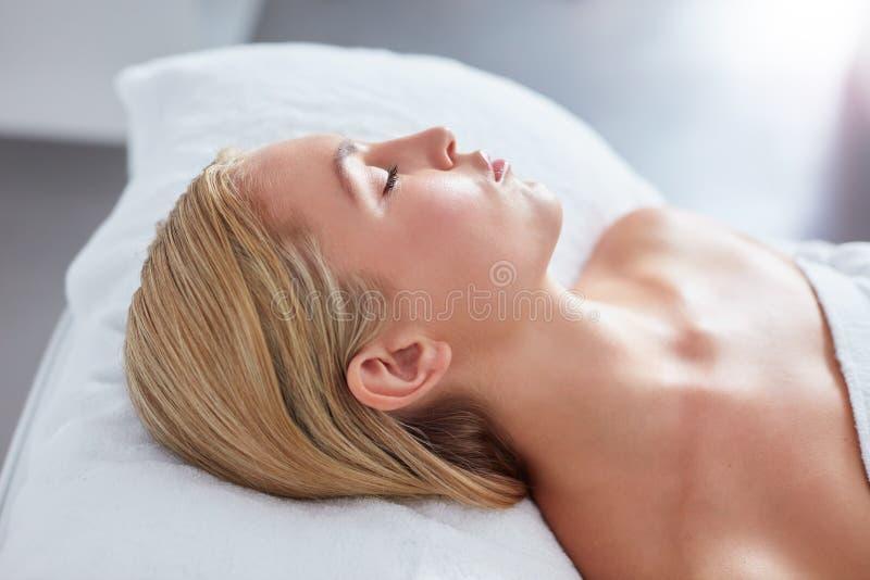 Donna giovane che si distende sulla Tabella di massaggio immagini stock libere da diritti