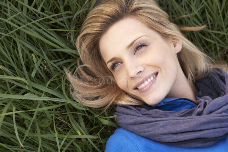 Donna giovane che si trova da solo sull'erba fotografia stock