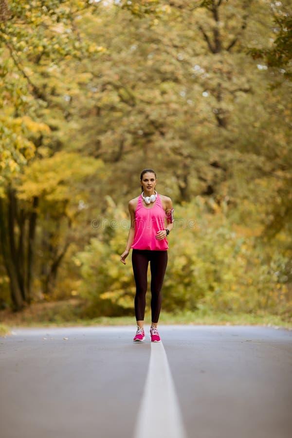 Donna giovane di forma fisica che corre alla traccia della foresta in autunno fotografie stock
