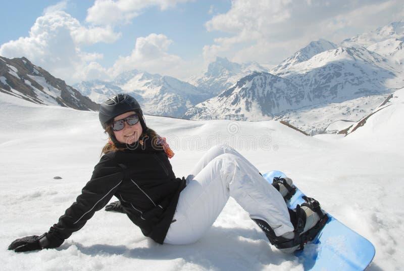 Donna giovane di risata che si siede nella neve con snowboar fotografie stock