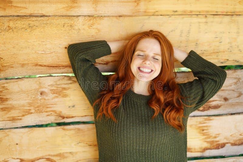 Donna giovane felice della testarossa con un sorriso kitsch immagini stock