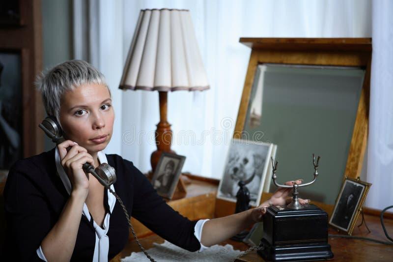 Donna giovane sul vecchio telefono immagini stock