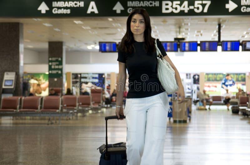 Donna gli che porta bagaglio in aeroporto fotografia stock
