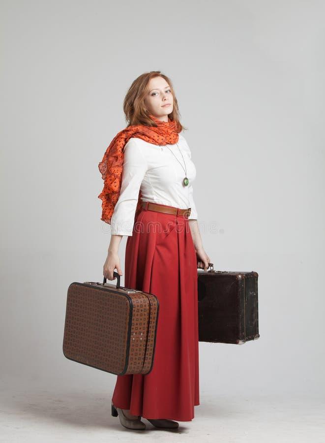 Donna in gonna rossa d'annata con le valigie immagine stock libera da diritti