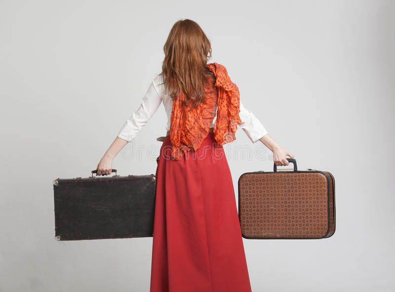 Donna in gonna rossa d'annata con le valigie fotografia stock libera da diritti