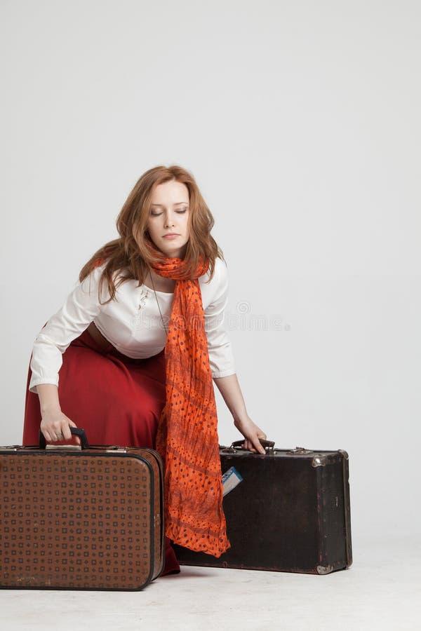 Donna in gonna rossa d'annata con le valigie immagini stock