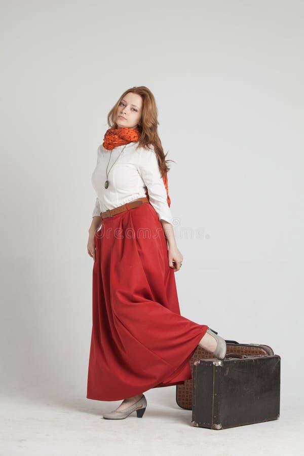 Donna in gonna rossa d'annata con le valigie immagini stock libere da diritti