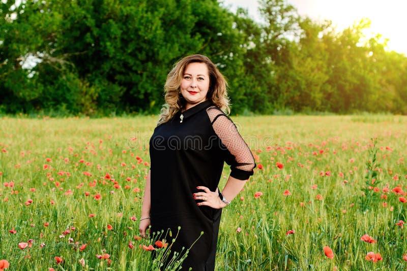 Donna graduata più in un vestito nero su un campo di grano verde e dei papaveri selvatici Donna grassa di peso eccessivo immagini stock libere da diritti