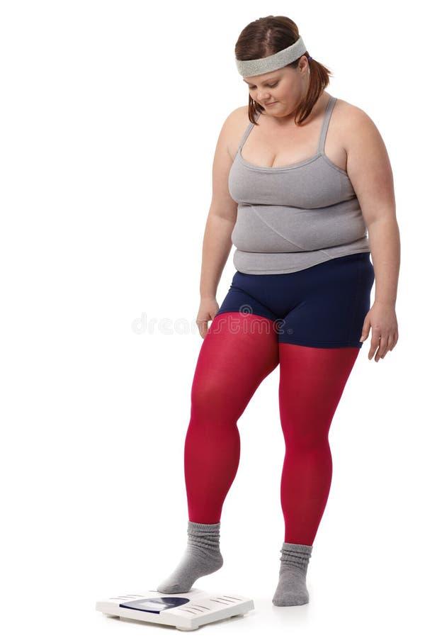 Donna grassa che fa un passo sulla scala fotografia stock