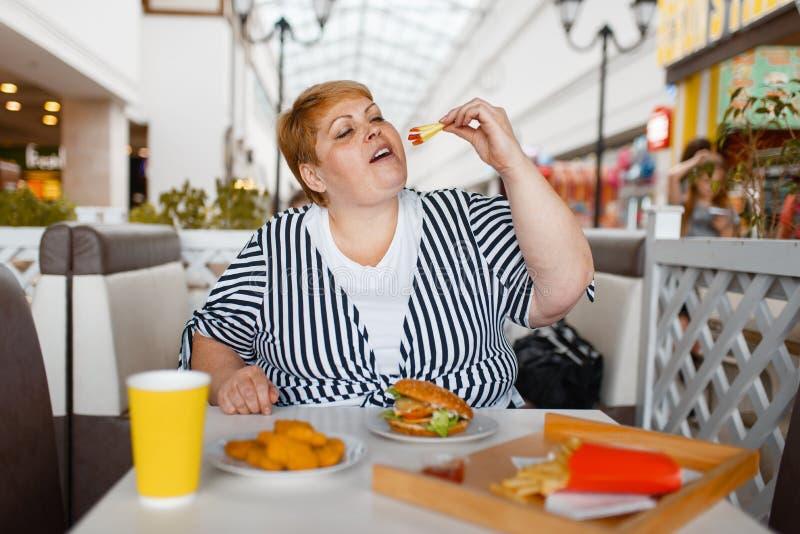 Donna grassa che mangia hamburger nella corte di alimento del centro commerciale fotografia stock libera da diritti