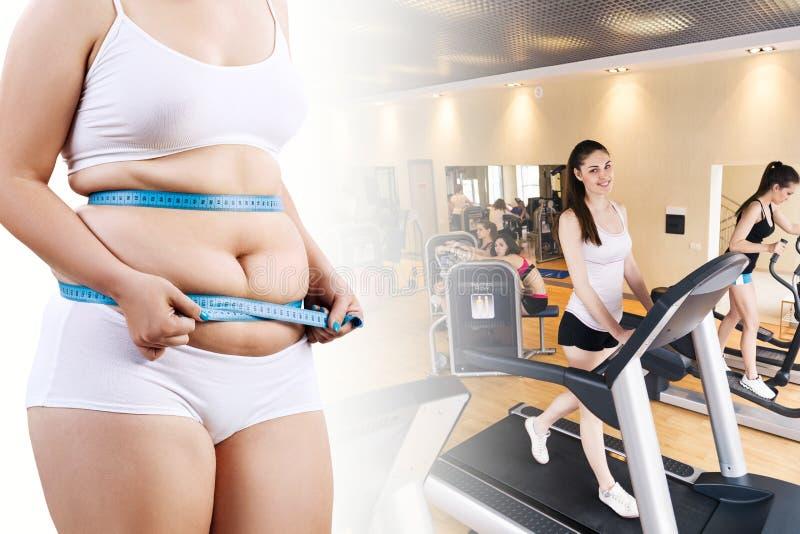 Donna grassa che misura la sua pancia sopra le donne sportive nella palestra immagini stock libere da diritti