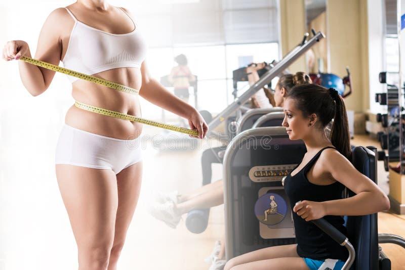 Donna grassa che misura la sua pancia sopra le donne sportive nella palestra fotografia stock