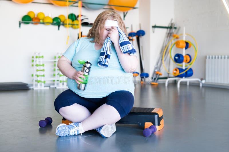 Donna grassa esaurita dopo l'allenamento fotografia stock