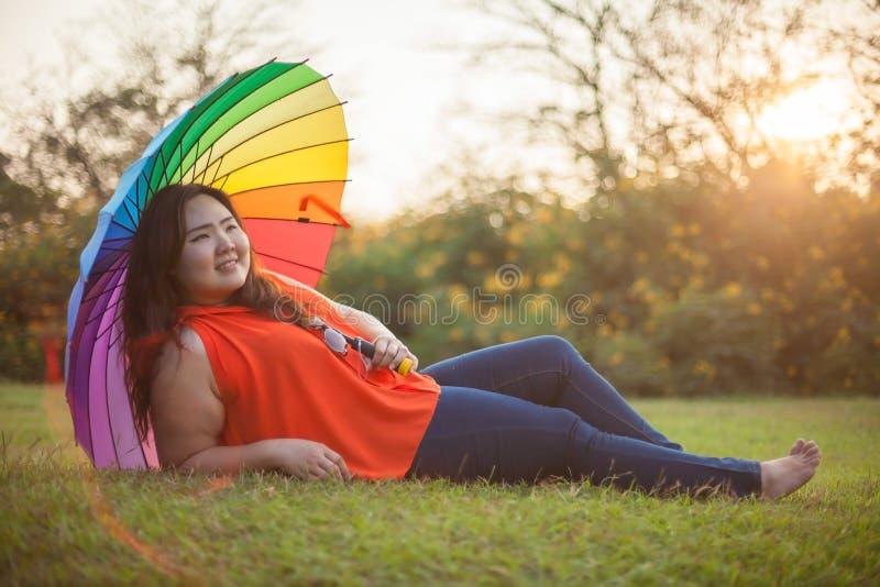 Donna grassa felice con l'ombrello immagini stock
