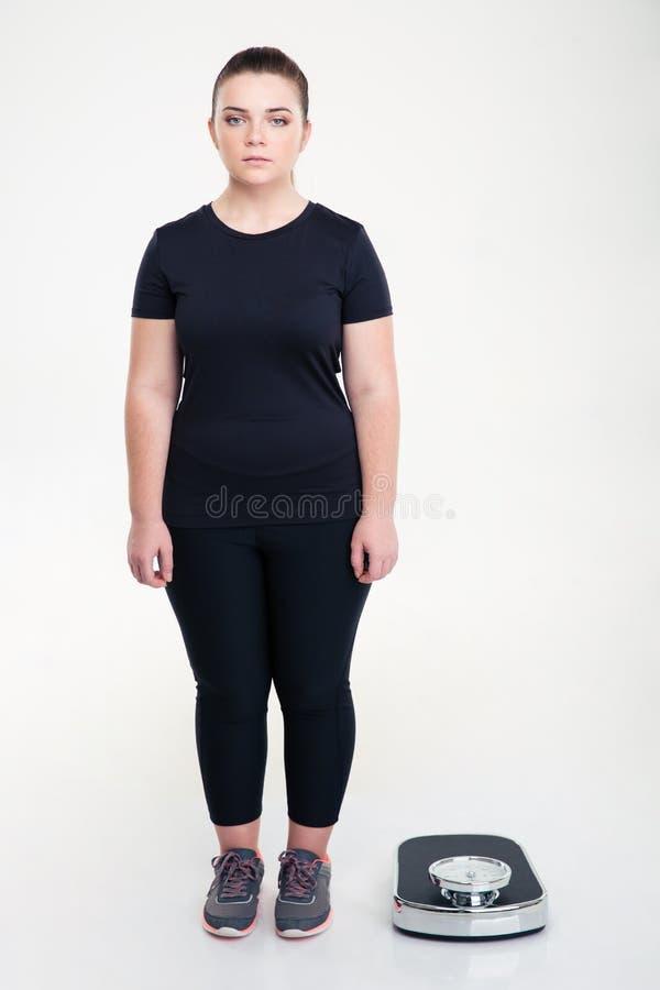 Donna grassa seria che sta vicino alla bascula immagini stock libere da diritti