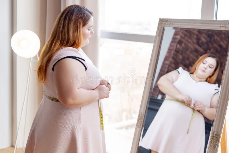 Donna grassottella piacevole che esamina lo specchio immagini stock libere da diritti