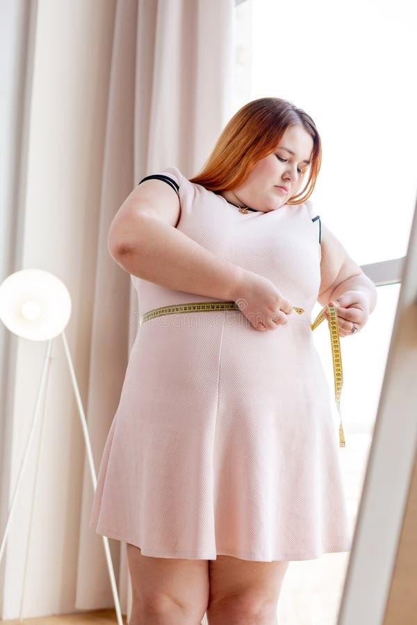 Donna grassottella piacevole che prova a misurare la sua vita fotografia stock libera da diritti