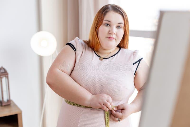 Donna grassottella seria che pensa al suo peso immagine stock