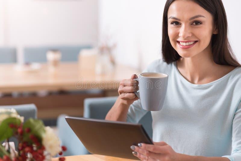 Donna graziosa affascinante che mangia un caffè fotografia stock libera da diritti