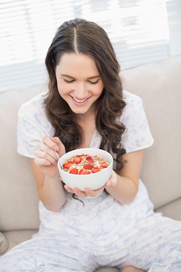 Donna graziosa allegra in pigiami che mangia cereale fruttato fotografia stock libera da diritti