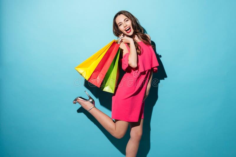 Donna graziosa allegra in vestito che tiene i sacchetti della spesa variopinti immagini stock