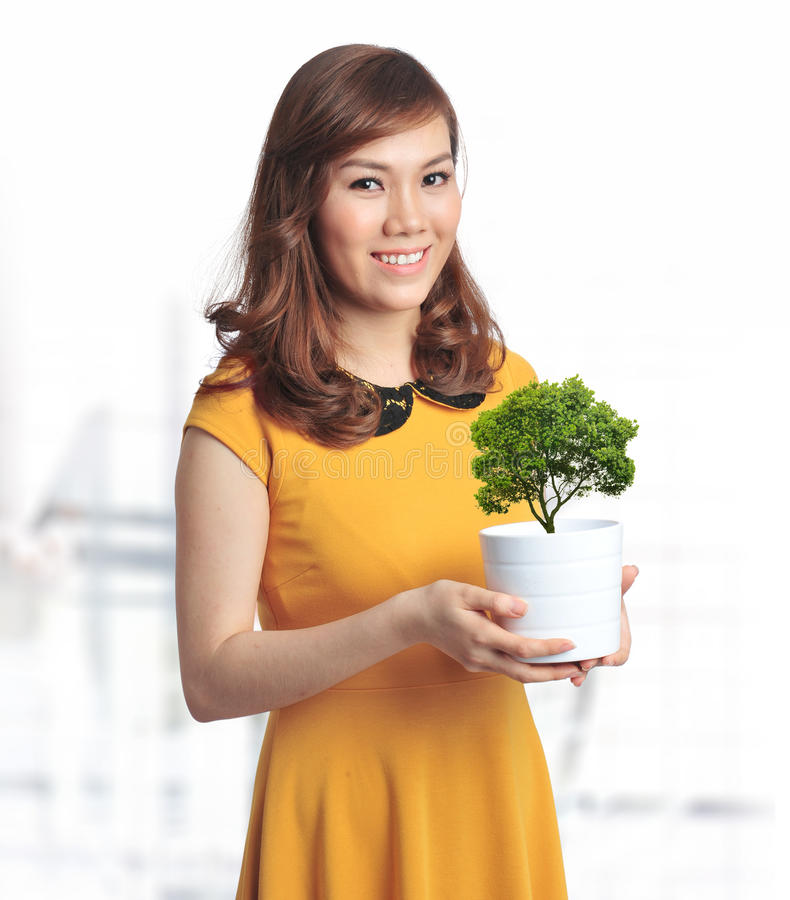 Donna graziosa asiatica con una pianta verde in un POT immagini stock