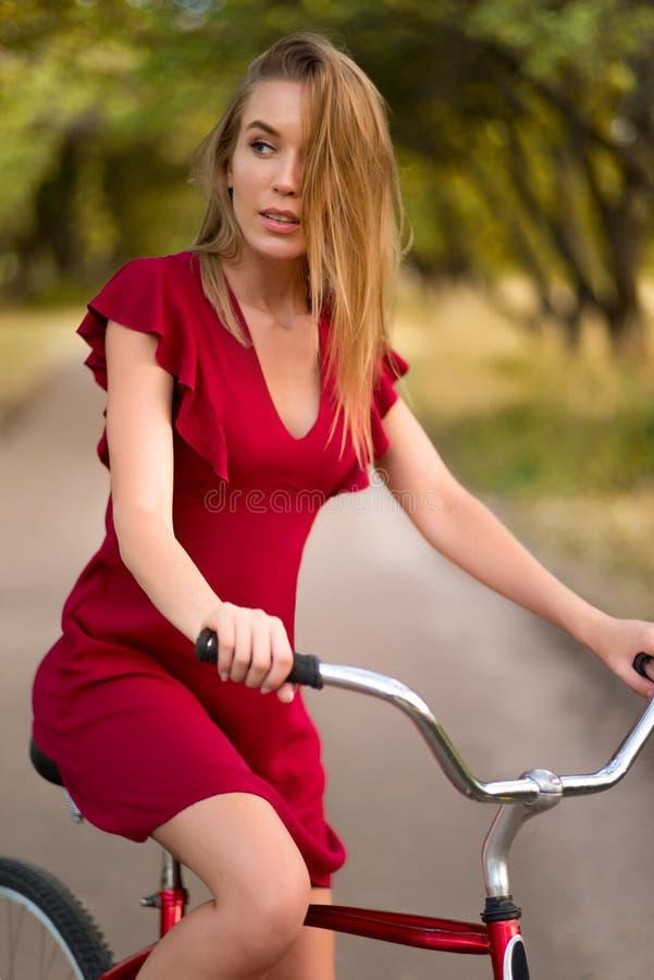 Donna graziosa in bicicletta rossa dell'annata di guida del vestito immagine stock libera da diritti