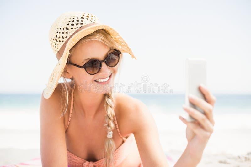 Donna graziosa in bikini ed occhiali da sole che prendono un selfie sulla spiaggia fotografia stock