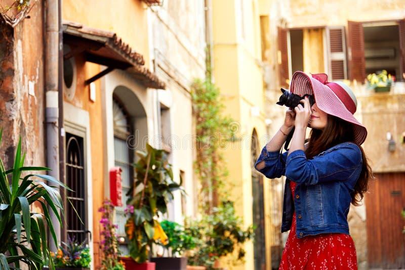 Donna graziosa in cappello che tende con la macchina fotografica a Trastevere a Roma, Italia immagine stock libera da diritti