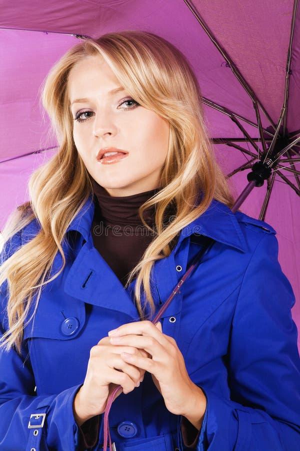 Donna graziosa in cappotto blu con l'ombrello immagine stock libera da diritti