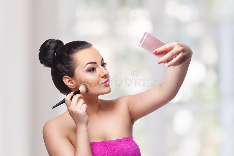 Donna graziosa che applica bronzer sopra immagini stock