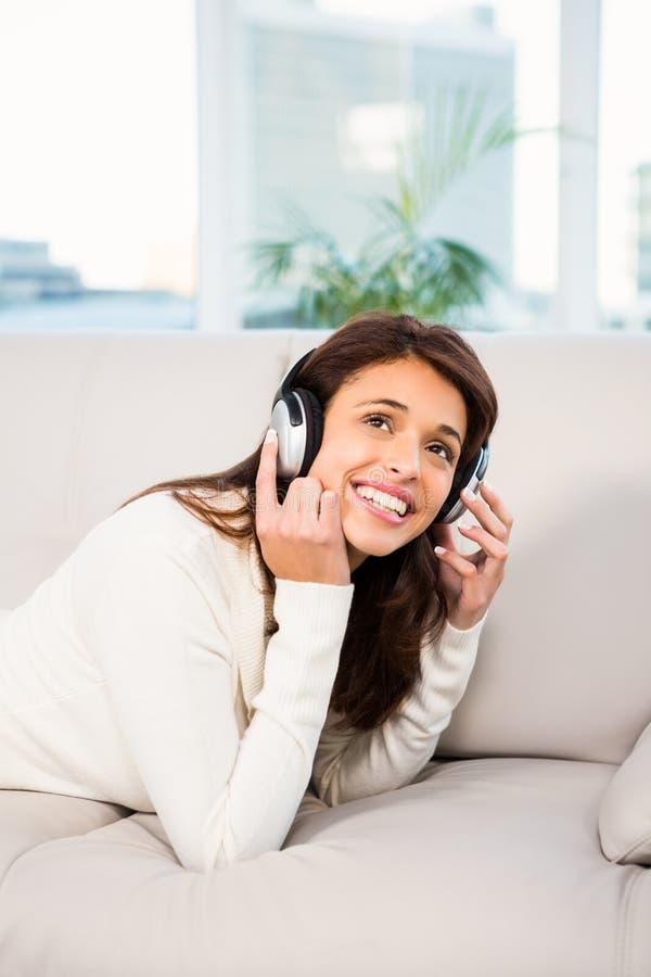 Donna graziosa che ascolta con le cuffie la musica che si trova sullo strato fotografie stock libere da diritti