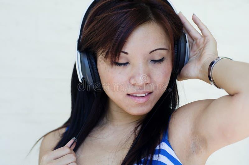 Donna graziosa che ascolta la musica con le cuffie fotografia stock