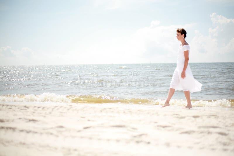 Donna graziosa che cammina la spiaggia immagini stock