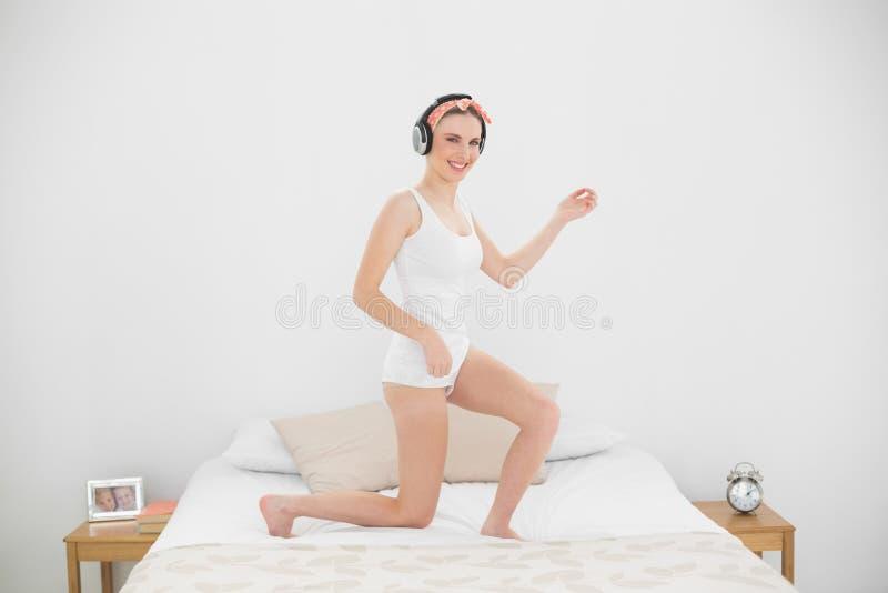 Donna graziosa che gioca Air guitar sul suo letto immagine stock