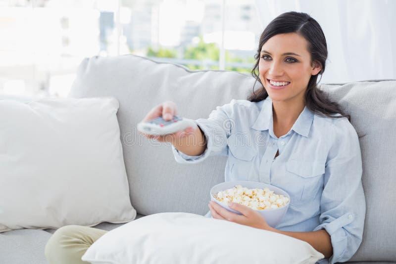 Donna graziosa che guarda TV mangiare popcorn immagini stock