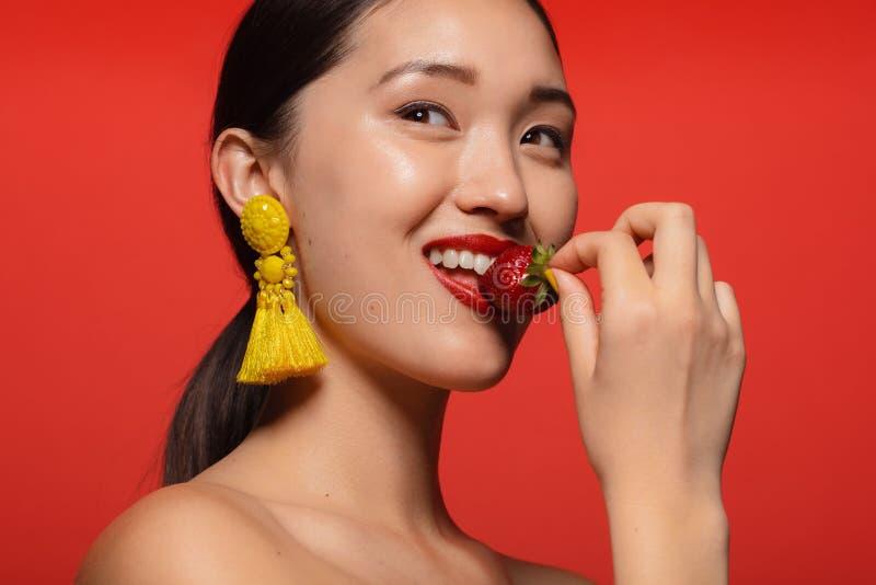 Donna graziosa che mangia fragola fresca fotografia stock