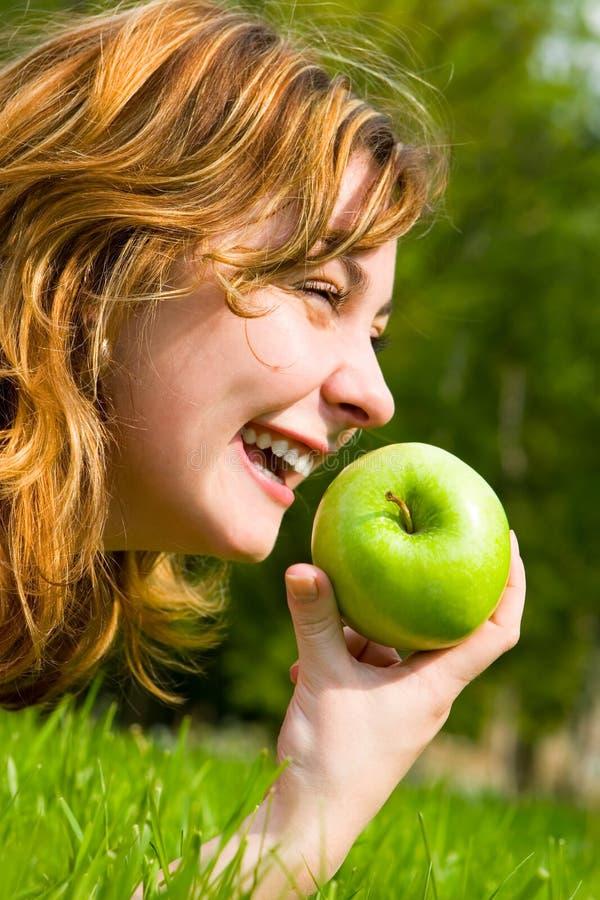 Donna graziosa che mangia mela verde immagini stock