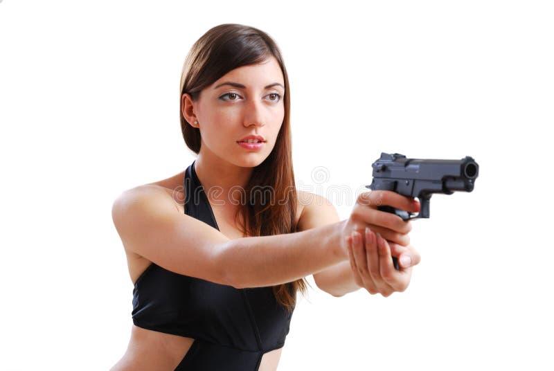 Donna graziosa che mira una pistola. fotografia stock libera da diritti