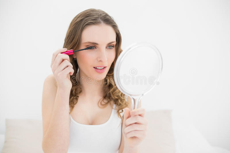 Donna graziosa che per mezzo della mascara fotografia stock
