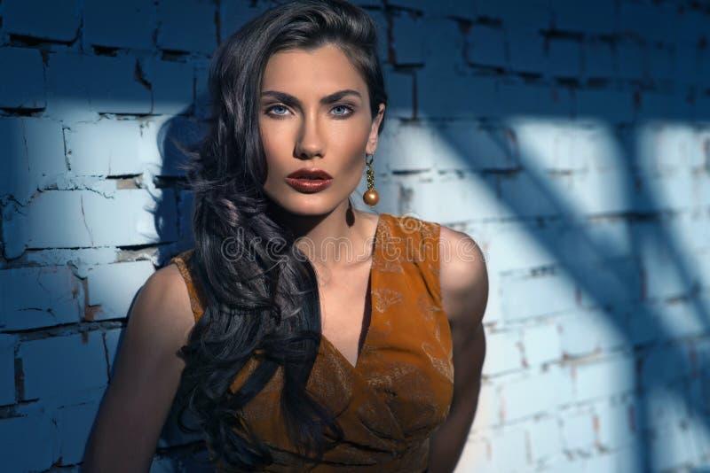Donna graziosa che posa alla parete, vestito arancio luminoso alla moda d'uso fotografie stock