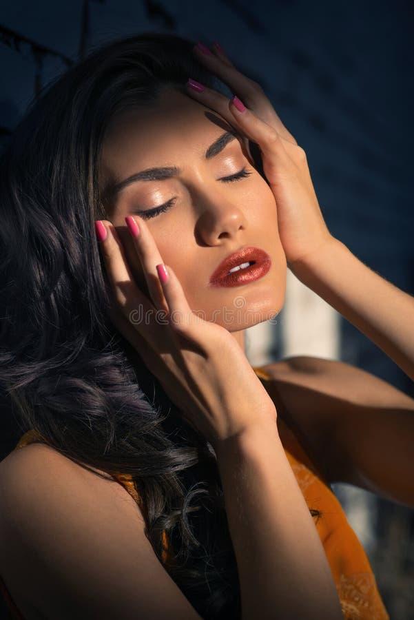 Donna graziosa che posa alla parete, vestito arancio luminoso alla moda d'uso fotografia stock