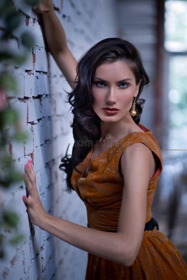 Donna graziosa che posa alla parete, vestito arancio luminoso alla moda d'uso immagini stock libere da diritti
