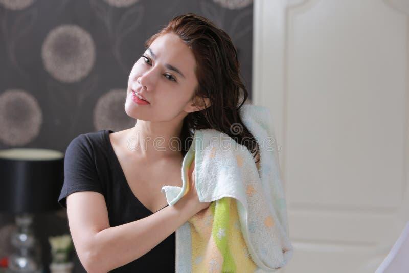 Donna graziosa che pulisce i suoi capelli con l'asciugamano di bagno fotografia stock