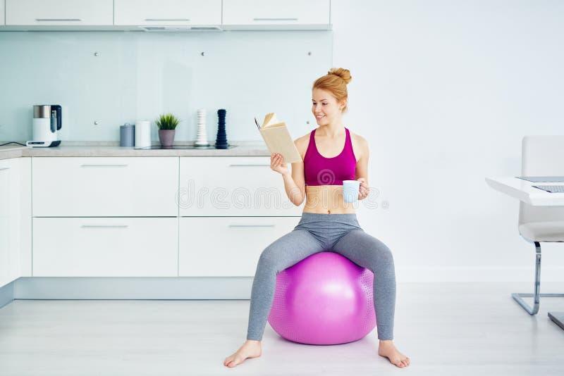 Donna graziosa che riposa dopo l'allenamento di forma fisica a casa immagine stock
