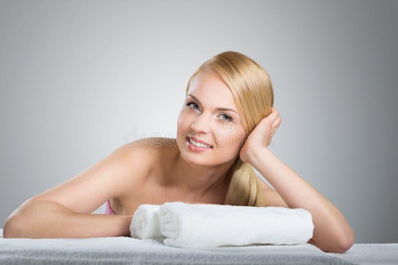 Donna graziosa che si appoggia tavola con sorridere degli asciugamani immagini stock libere da diritti