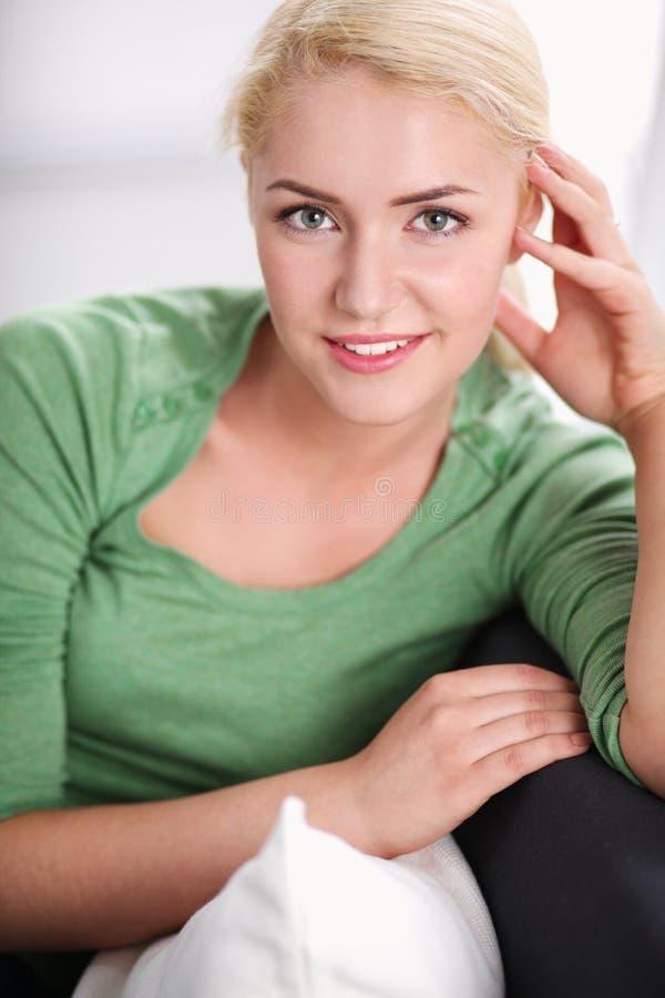 Donna graziosa che si rilassa sullo strato a casa nel salone fotografia stock libera da diritti