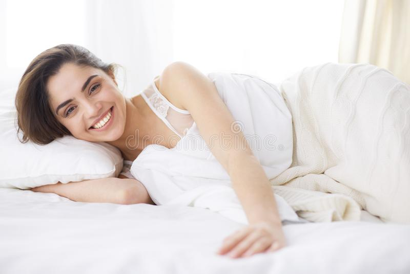 Donna graziosa che si riposa sul suo letto a casa immagine stock