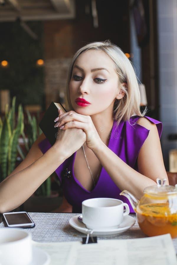 Donna graziosa che si siede nel ristorante, tisana bevente fotografie stock libere da diritti